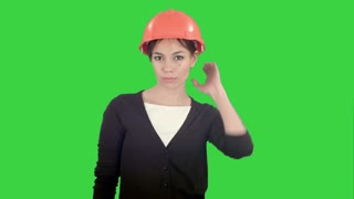 Female construction worker in helmet making funny dancing on a Green Screen, Chroma Key