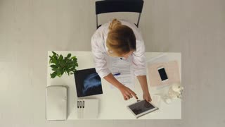Female doctor makes selfie on tablet in medical office