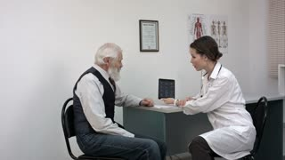 Female doctor reviewing x-ray on a tablet with mature patient.