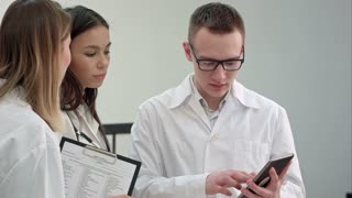 Female doctor showing something on tablet to her medical team