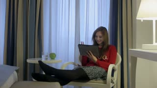 Female have video call using digital tablet in hotel room