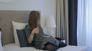 Female listening to the music and rubs hand cream on the bed at hotel