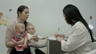 Female pediatrician doctor explain something to mother with newborn baby twins at modern hospital indoors