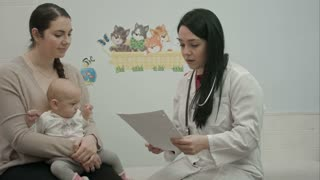 female pediatrician doctor shows some papers to woman with small baby