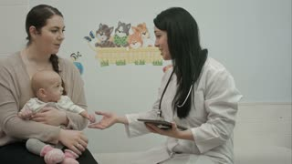 female pediatrician doctor shows something on tablet  to woman with small baby