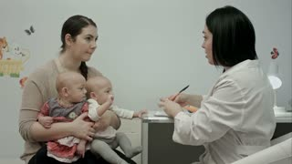 Female pediatrician doctor's explaining something to mother with newborn twins and writing a prescription for drugs