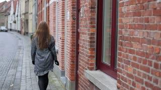 Female walking away from camera at european street