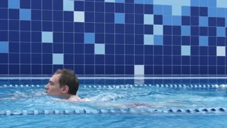 Fit swimmer doing the breaststroke in a swimming pool