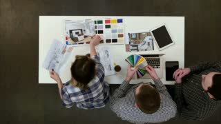 Four designers discussing layouts and color samples at office desk