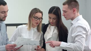Four young office coworkers going through business presentation