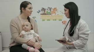 friendly pediatrician doctor explain something to mother with newborn baby