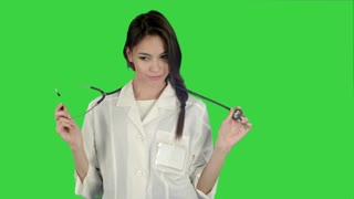 Funny female doctor playing with a stethoscope on a Green Screen, Chroma Key