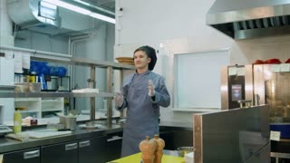 Funny young male cook dancing in the professional kitchen
