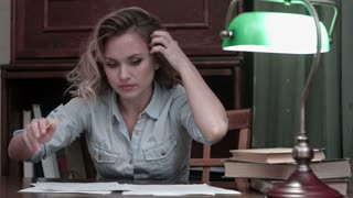 Furious woman stressingly making notes and tearing up documents at her workplace