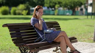 Girl happy talking by smart phone in a park seating at bench