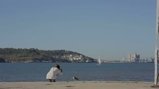 Girl  playing with sea gull and looking at the river in portugal belem embankment