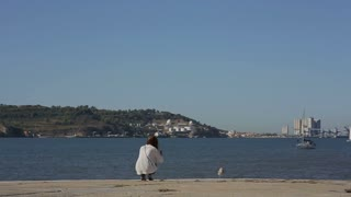 Girl  takeing picture of yacht and albatros at the river in portugal belem embankment