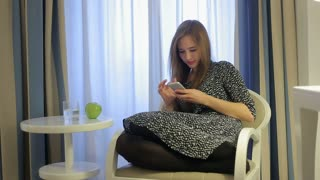 Girl texting on smartphone in hotel room and drink water from glass