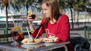 Girl toasts to camera with glass of asngria alone in a street cafe