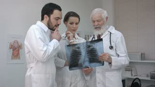 Group of doctors and nurse looking at X-ray.