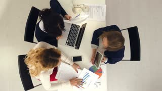 Group of female marketers works in the office with documents and diagrams