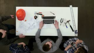 Group of young architects working on drawings and making measurements with ruler and divider
