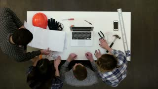 Group of young architects working on drawings