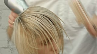 Hairdresser drying woman's hair using hair dryer