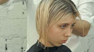 Hairdresser trimming hair with scissors