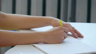 Hand of young girl write on notebook in scholl or colledge.