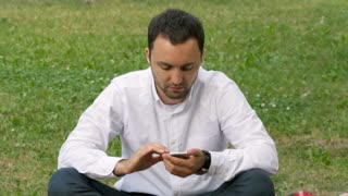 Handsome adult man sending a text message using cell phone at sunny evening outdoors in park