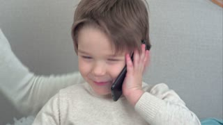 Handsome little boy talking on the phone