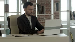 Happy business man finished his work in office with notebook