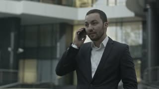 Happy businessman answering call and talk with busness partner standing outside the office