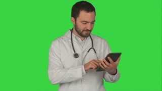 Happy doctor using digital tablet on a Green Screen, Chroma Key