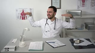 Happy excited doctor making strange gestures dancing at workplace