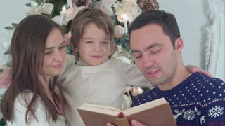 Happy family of three reading together on Christmas evening