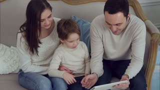 Happy family of three watching funny videos on tablet