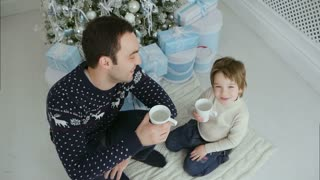 Happy father and his son with cups sitting near the Christmas tree and looking at the camera