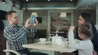 Happy father taking photo of his wife kissing their daughter by smartphone at restaurant