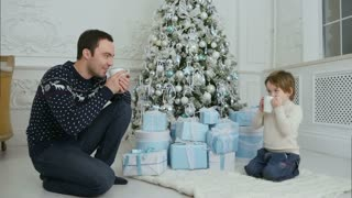 Happy father with his son sitting near the Christmas tree and drinking hot tea