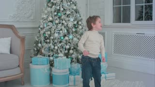 Happy little boy dancing next to the Christmas tree and presents