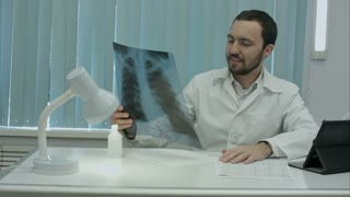 Happy male doctor working at office, writeing, smiling.