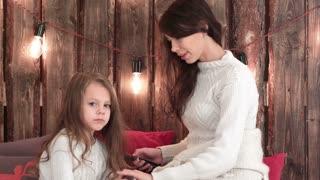 Happy mother combing her daughter's hair