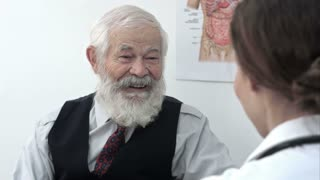 Happy senior patient talking to the doctor.