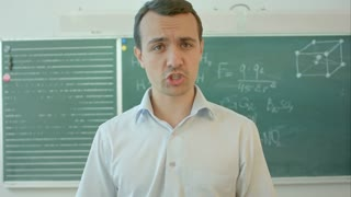 Happy smiling teacher or student man standing near chalkboard, talking on camera
