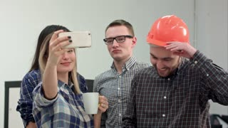 Happy young architects taking funny selfies in office