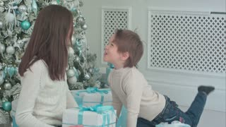 Happy young mother with cute little son playing around with Christmas presents