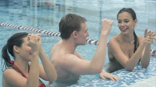 Happy young people dancing in the swimming pool