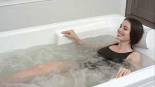 Happy young woman relaxing in jacuzzi spa